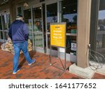 Small photo of Fontana, California/United States - 01/26/2020: A man enters a Whole Foods Market grocery store and passes a sign that says Amazon returns drop off.