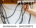 Small photo of Concept of clutter in office. Unwound and tangled electrical wires under the table.