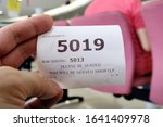 Small photo of Hand holding a queue number ticket for a counter service at a bank while waiting turn to be attended to. A queue ticket showing the current waiting number been assigned.