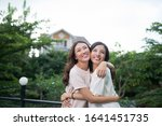 Two Young Asian Woman Hugging...