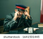 Small photo of Modern cosplay retro clothing and mid-20th century surroundings The Soviet security officer, an employee of the All-Russian Extraordinary Commission to Combat Counter-Revolution and Sabotage, wears a