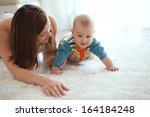 mother with her baby playing on ... | Shutterstock . vector #164184248