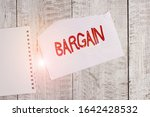 Small photo of Conceptual hand writing showing Bargain. Business photo text Negotiate terms and conditions of transaction ask for discount Torn paper and notebook sheet placed above classic wooden table.
