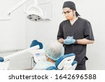 Small photo of Patient and dentist during implant placement operation. Real operation. Tooth extraction, implants. Professional uniform and equipment of a dentist. Healthcare Equipping a doctor's workplace.