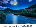 wild river flowing between green mountains on a clear summer night - stock photo