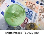 Glass world and Euro currency depicting global finance - stock photo
