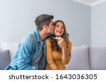 Small photo of Joyful couple finding out results of a pregnancy test at home. Happy couple looking at pregnancy test. Woman surprising her husband with positive pregnancy test, he seems reasonably pleased