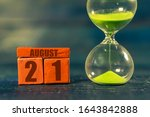 august 21st. Day 20 of month,Handmade wood cube with date month and day and hourglass with green sand. Time passing away. artistic coloring.  summer month, day of the year concept