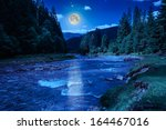 river near  forest at the foot of mountain at night - stock photo