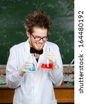 Small photo of Mad professor laughs keeping two flasks with colored liquid in his laboratory