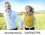 cheerful senior couple running... | Shutterstock . vector #164560796