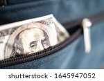 Dollar. The money stew peeps out of the pocket. Concept - money is hidden. Dollars are hiding in a person?s pocket. Cash peeping out of the wallet. Use of cash. Concept - cash risk. - stock photo
