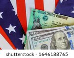 Small photo of USA dollar cash banknote stimulus economic tax return check with US flag