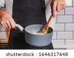 Small photo of Man's hands close-up holding a saucepan and stirring with wooden spoon. Cooking dinner at home.