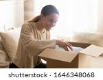 Small photo of Smiling millennial woman sit on couch at home open post package shopping online buying goods on internet, happy young female customer unpack postal shipping parcel satisfied with order or delivery