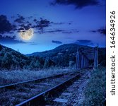 mountains landscape. rail metal bridge in moon light - stock photo