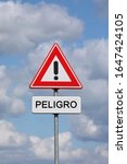 Small photo of A sign with a exclamation mark warning for a dangerous situation ahead and a smaller sign below with the Spanish word Peligro on it, meaning danger in English