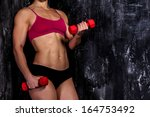 muscled woman with barbells  | Shutterstock . vector #164753492