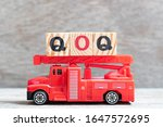 Small photo of Red fire truck hold letter block in word QOQ (abbreviation of quarter on quarter) on wood background
