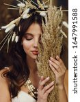 Small photo of Portrait of handsome woman with amazing large chaplet on head, beautiful make up and necklace. Attractive girl closing eyes, holding by hands wheats and hiding face behind them.