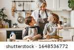 Small photo of happy family grandmother and grandchildren cook in the kitchen, knead dough and bake cookies