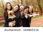 Stock photo huge group of women showing thumbs up for a cute little pet dog 164865116