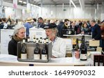 Small photo of Strasbourg, France - Feb 16, 2020: Beautiful adult couple selling French wine at the Vignerons independant English: Independent winemakers of France wine fair for private and horeca customers