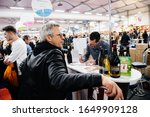 Small photo of Strasbourg, France - Feb 16, 2020: French man waiting for his order at Vignerons independant English: Independent winemakers of France wine fair for private and horeca customers