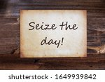 Small photo of Old Paper, English Text Seize The Day, Wooden Background
