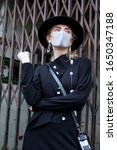 Small photo of London, UK - 15 February, 2020 People wear mask for protection during London fashion week. Street style. Stylish woman in black dress, coat and a wide-brimmed hat wears a beige mask. Fashion week