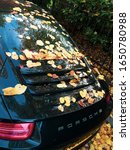 Small photo of London, United-Kingdom - october 2015: Leaves falling on the rear bonnet of a brand new Porsche 911 parked in London on an autumn day. Change on the automobile industry from fuel to electric engine.