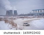 "Small photo of Russia, Novosibirsk - November 30, 2019. Russian old white car ""VAZ-Zhiguli"" is fast drifting sideways, raising snow behind him on the turn behind the pipes of the thermal power plant in winter."
