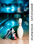 Small photo of selective focus of bowling shoes, ball and skittle on bowling alley