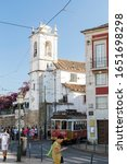 Small photo of Lisbon, Portugal - September 8, 2019: Tourists and traditional tram in front of the Igreja de Santa Luzia church at Largo das Portas do Sol in the Alfama district in downtown Lisbon, Portugal.