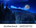 pine forest and lake near the mountain early at night - stock photo