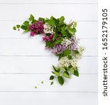 Small photo of Wreath from purple lilac flowers on white wooden background. Surprise for lovely woman. Natural spring style. Aromatherapy. Flowers Flat lay, top view. Background with copy space. Spring blossom mood