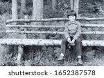 USSR, WESTERN UKRAINE - CIRCA 1982: Vintage photo of little boy Sergey Tsyukevitch sitting on wooden bench in forest in Western Ukraine, USSR