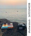 Small photo of February 20,2020, Goa: Gail Honeyman book and camera by the seaside