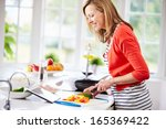 woman in kitchen following... | Shutterstock . vector #165369422