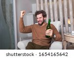 Small photo of Fanatic sports fan man watching soccer game on tv celebrating. Attractive, happy guy watching football, celebrating victory of his favorite team, having beer, sitting in living room