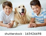 Stock photo portrait of happy siblings with their pet having rest at home 165426698