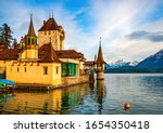 Scenic view of amazing Oberhofen castle reflected in water of Lake Thun and illuminated by sunset light. Snowcapped mountains and picturesque sky on background, Switzerland - stock photo