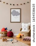 Small photo of Stylish scandinavian interior of child room with natural toys, hanging decoration, design furniture, plush animals, teddy bears and accessories. Interior design of kid room. Mock up poster frame.