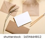 Small photo of White empty paper card with stationery set of envelopes, notebook, pencil. Blank card styled mockup on beige background. To do list, greeting card or writing a letter concept.