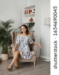 Small photo of Fashion shot of a young beautiful woman in a short dress sitting in armchair. Portrait of a model girl with curly hair and slim body in light spring dress in the interior. Spring fashion. Summertime