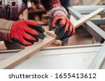 Worker marks with pencil a plywood for cutting on a circular saw