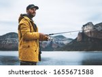 Small photo of beard fisherman hold in hand fishing rod, man enjoy hobby sport on mountain river, person catch fish on background nature blue sky, fishery concept