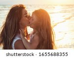 Small photo of Mom and daughter on the seashore on a sunny summer evening. Manifestation of maternal love