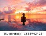 Small photo of Paradise luxury resort honeymoon getaway destination at idyllic Caribbean tropical landscape hotel, woman silhouette swimming in infinity pool watching sunset serene. Winter getaway at dusk.
