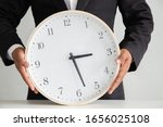 Small photo of Businessman holding a clock ready to work Strategy and time management in the office, Concept: symbol manage at deadline professional for success, Time to take a summer vacation, manager hour job
